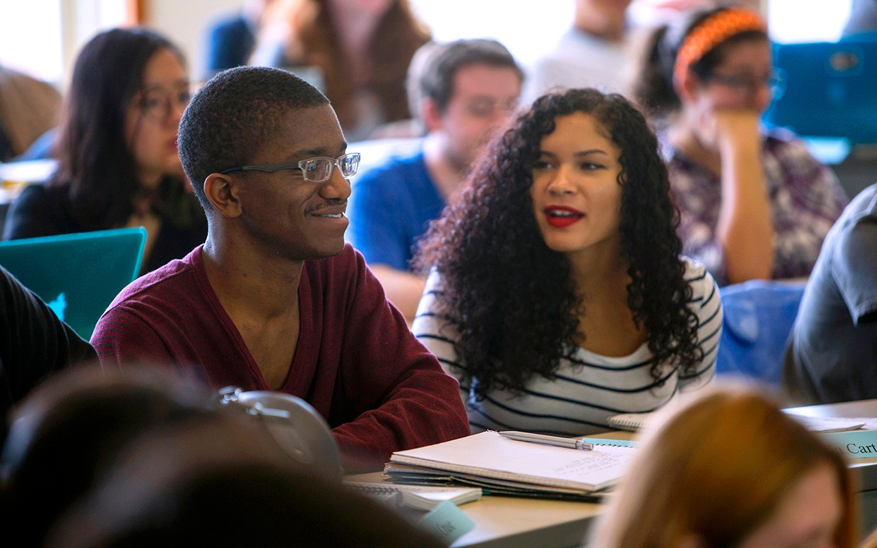 Two students smile while sitting in a CCM Music Theory and Composition classroom.