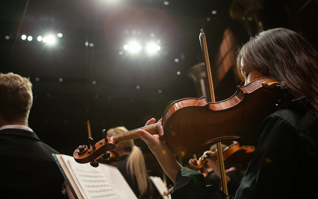 Female violin student performs onstage under lights with the CCM Concert Orchestra