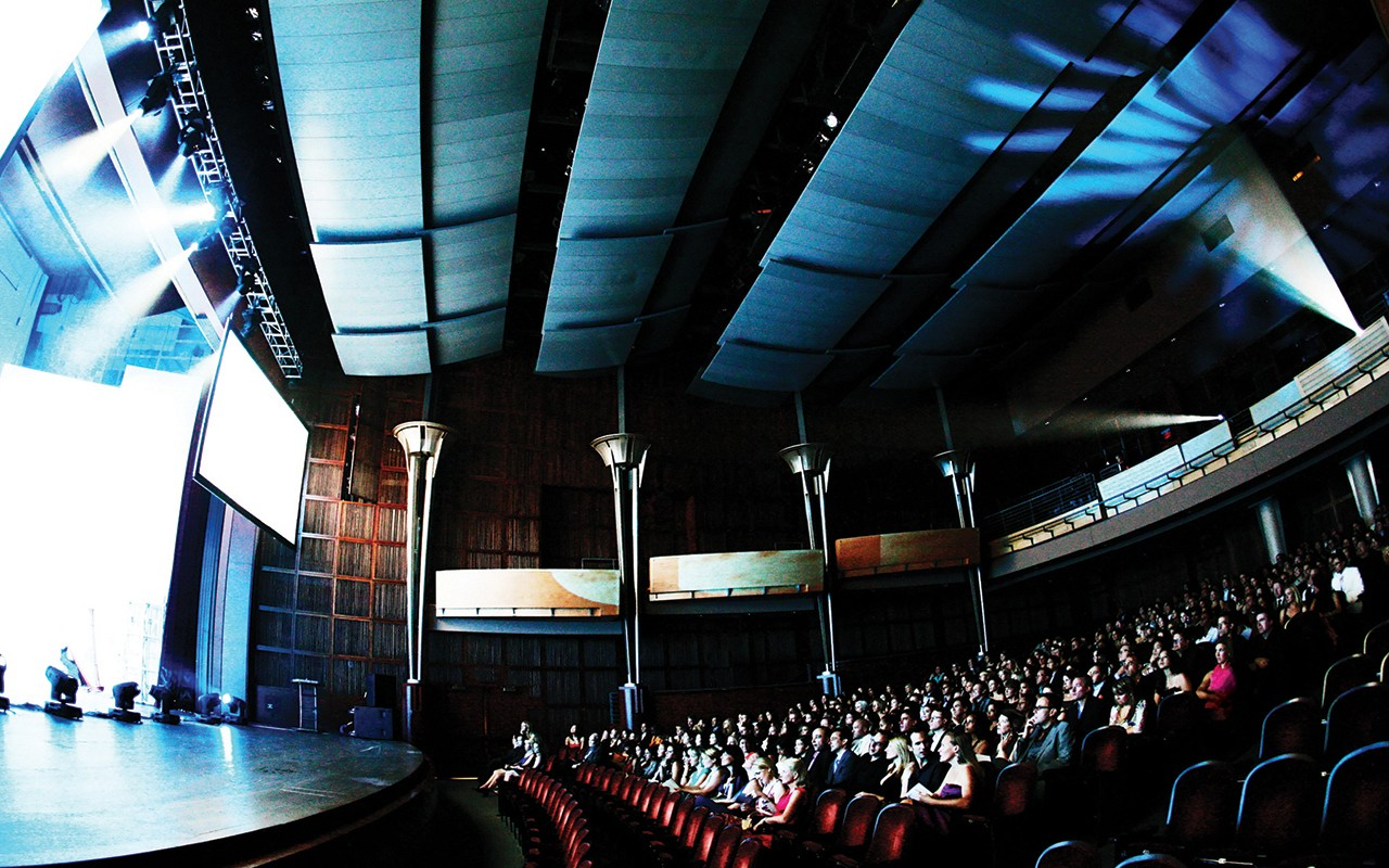 Stage lighting reveals a side view of audience sitting in Corbett Auditorium